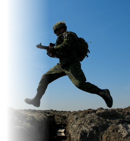 A Canadian Armed Forces member jumping a trench